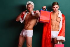 Handsome macho santa twins. Young handsome macho santa tough twins with sexy muscular athletic strong body has bare torso and strong belly in christmas cape or Royalty Free Stock Image