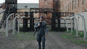 A young handsome male actor dressed as a German soldier walks towards camera. The reconstruction of a concentration camp. A young male reenactor dressed as a stock video footage