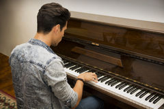 Young handsome male artist playing classical upright piano. Young handsome male artist playing his wooden classical upright piano, indoor portrait Royalty Free Stock Photos