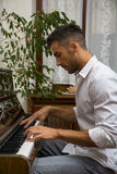 Young handsome male artist playing piano Stock Image