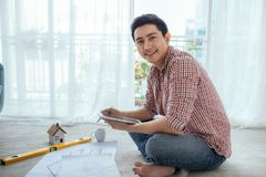 Young handsome male asian architect working at home on the floor Royalty Free Stock Photo
