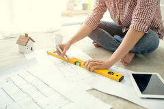 Young handsome male asian architect working at home on the floor Royalty Free Stock Photos