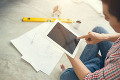 Young handsome male asian architect working at home using tablet on the floor Royalty Free Stock Images