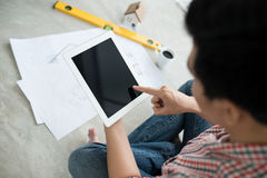 Young handsome male asian architect working at home using tablet on the floor. Royalty Free Stock Photography