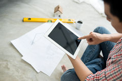 Young handsome male asian architect working at home using tablet on the floor. Stock Photo