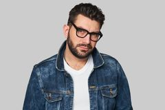 Casual man wears denim jacket and glasses. Young handsome male with beard, mustache and trendy hairdo. Casual man wears denim jacket and glasses. Serious guy Royalty Free Stock Photos