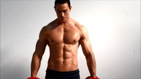 Young handsome male bodybuilder training obliques and abs muscles with dumbbells, against light background