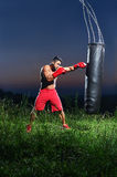 Young handsome male boxer practicing on a punching bag outdoors Stock Photography