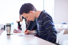 Young, handsome male college student sitting in a classroom full. Of students during class (color toned image; shallow DOF Stock Photo