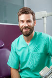 Young handsome male doctor with beard smiling with white teeth. Portrait of young handsome attractive male doctor with beard in green costume sitting in dental Stock Image