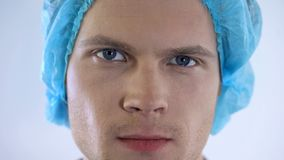 Young handsome male doctor face, surgeon posing confidently for camera closeup stock image