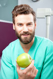 Young handsome male doctor smiling holding green fresh apple. Portrait of young handsome male doctor with beard smiling with perfect straight white teeth holding Royalty Free Stock Images