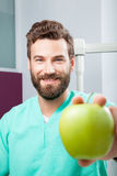 Young handsome male doctor smiling holding green fresh apple. Portrait of young handsome male doctor with beard smiling with perfect straight white teeth holding Stock Photos