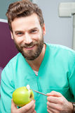 Young handsome male doctor smiling with white teeth holding apple. Portrait of young handsome male doctor with beard smiling with perfect straight white teeth Stock Photo