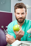Young handsome male doctor smiling with white teeth holding apple. Portrait of young happy handsome male doctor with beard smiling with perfect straight white Stock Images
