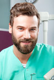 Young handsome male doctor smiling with white teeth. Portrait of young handsome attractive male doctor with beard in green costume sitting in dental clinic and Stock Photography