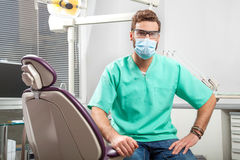 Young handsome male doctor wearing dentist mask and glasses. Portrait of young handsome male doctor in green costume wearing medical mask and glasses sitting in Royalty Free Stock Image