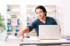 The young handsome male employee sitting at the office stock photo