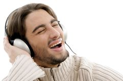 Young handsome male listening to music. With head phones against white background Stock Photography