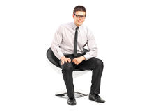 A young handsome male sitting on a chair Royalty Free Stock Photos