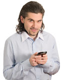 Young handsome male smiles and holds mobile phone Stock Photography