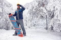 Young male snowboarder on the mountain. Young handsome male snowboarder on the mountain Stock Photos