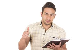 Young handsome male teacher holding notebook. With thumb up gesturing well done isolated on white Royalty Free Stock Photos