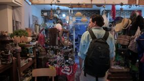 Young handsome man in an antique shop. Flea market in a tourist area. A tourist in the evening inspects