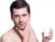 Young handsome man applying cream. Stock Photo