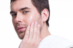 Young handsome man applying cream. Royalty Free Stock Images