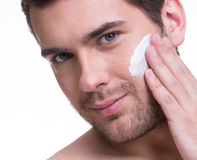 Young handsome man applying cream. Royalty Free Stock Photography