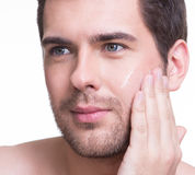 Young handsome man applying cream. Royalty Free Stock Image