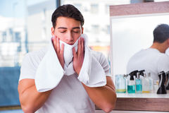 The young handsome man applying face cream Stock Photography