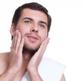 Young handsome man applying lotion. Royalty Free Stock Photo