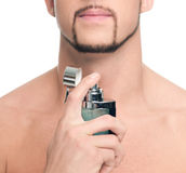 Young handsome man applying perfume Royalty Free Stock Photos