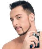 Young handsome man applying perfume Stock Image