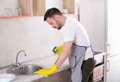 Man cleaning kitchen countertop. Young handsome man with apron and protective gloves wiping sink in kitchen. Husband doing chores royalty free stock images