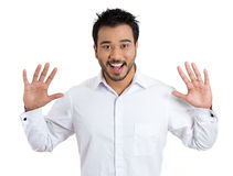 Young handsome man astonished at something unexpected, raising arms in the air Stock Photos