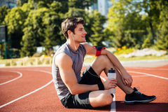 Young handsome man athlete resting at the stadium Stock Photos