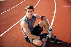 Young handsome man athlete resting at the stadium Stock Photo