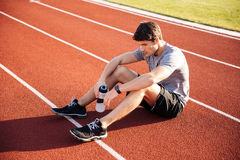 Young handsome man athlete resting with water bottle Stock Photos