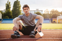 Young handsome man athlete resting with water bottle Royalty Free Stock Photography