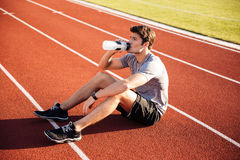 Young handsome man athlete resting with water bottle Royalty Free Stock Photos