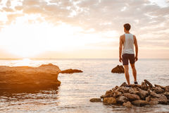 Young handsome man athlete standing at the rocky beach Royalty Free Stock Photography