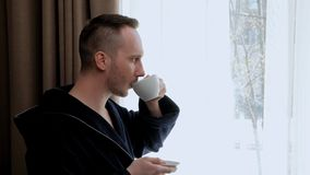 A young handsome man in a bathrobe stands at the window of the room and drinks tea or coffee from a white cup. Morning and the beginning of the day stock video footage