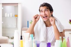 The young handsome man in the bathroom in hygiene concept royalty free stock images