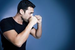 Young handsome man with beard and mustache studio portrait. Fisted hands, boxing concept against blue background Stock Images