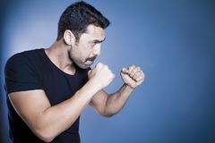 Young handsome man with beard and mustache studio portrait. Fisted hands, boxing concept against blue background Stock Photo