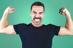 Young handsome man with beard and mustache studio portrait. Shouting and showing muscles, fisted hands, power and performance concept Stock Photography