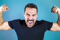 Young handsome man with beard and mustache studio portrait. Shouting and showing muscles, fisted hands, power and performance concept Stock Photo